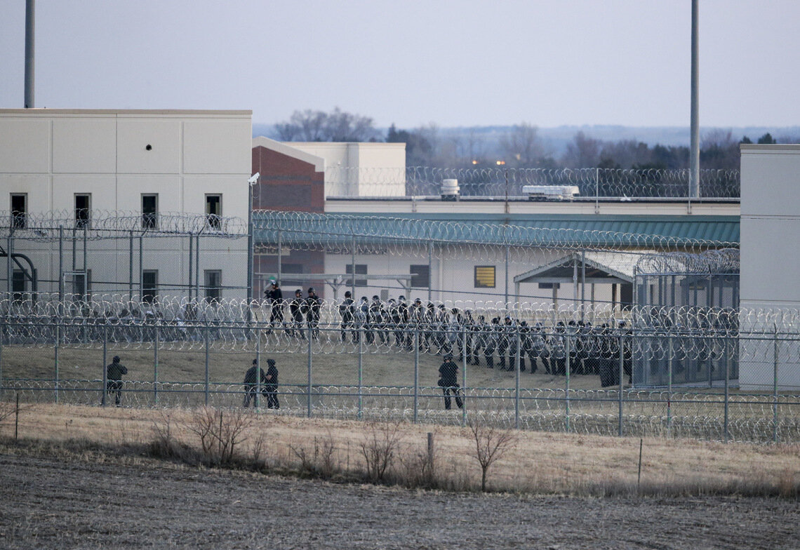 Security forces in riot gear amassed to confront dozens of incarcerated people who refused to return to their cells at Tecumseh State Correctional Institution in 2017.