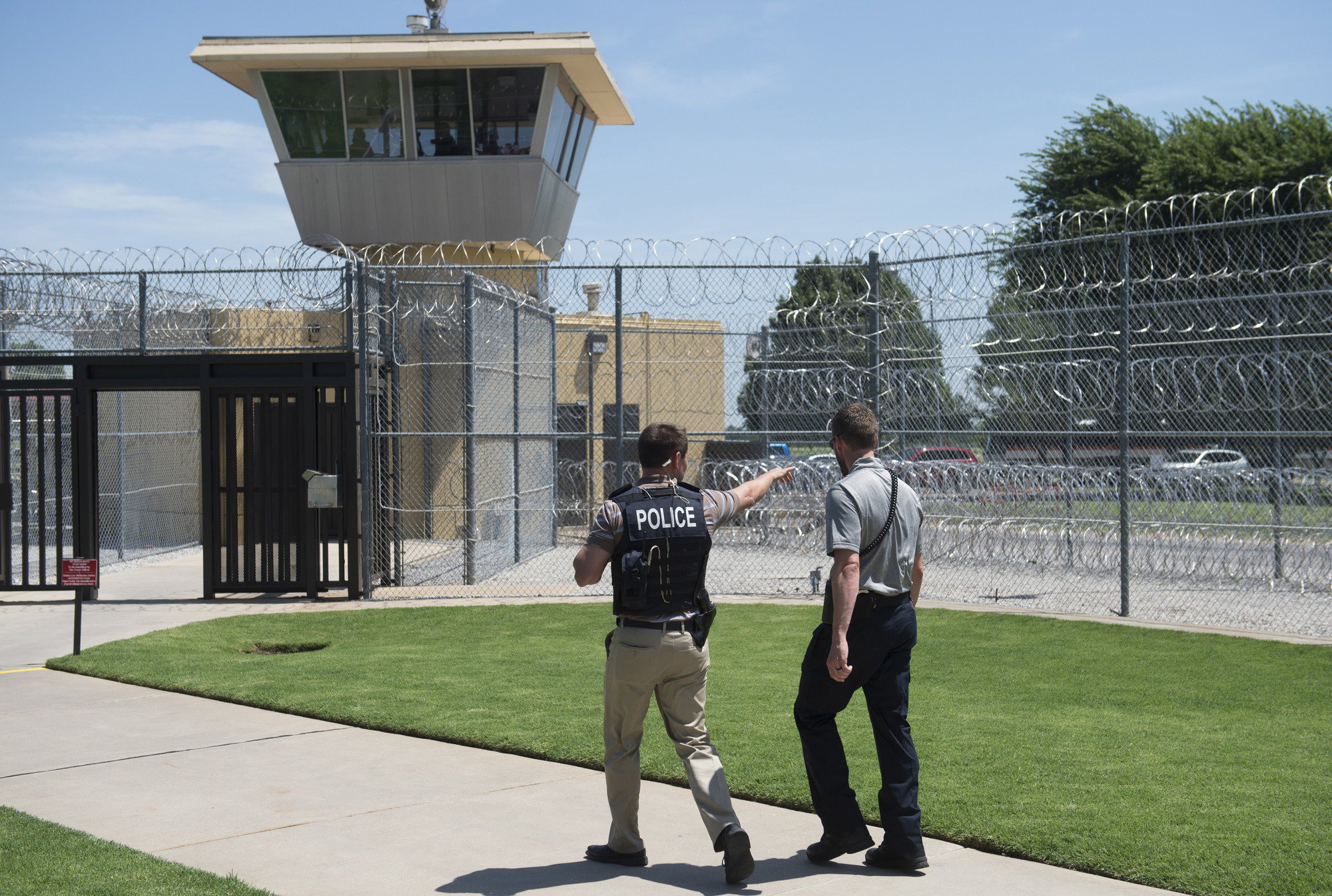 A police officer and a correctional officer patrol the entrance of the El Reno Federal Correctional Institution in El Reno, Oklahoma.
