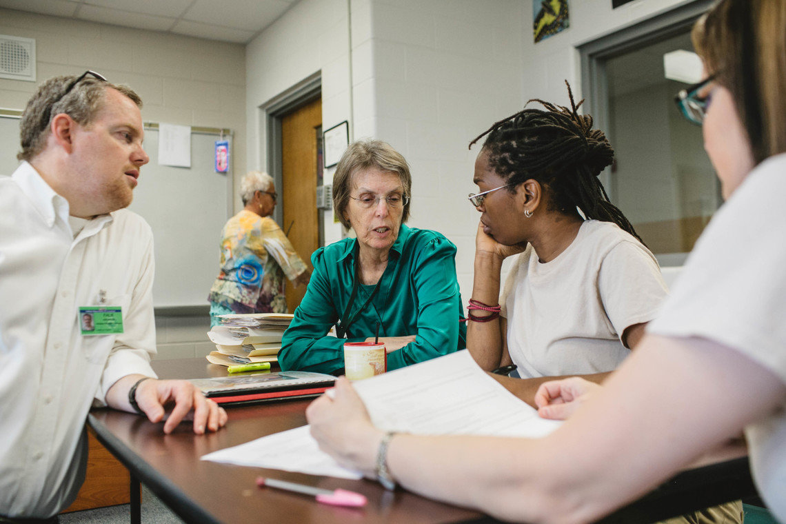 Andrew Falk, left, works with Kelsey Kauffman, center, Michelle Jones, center-right, and Natalie Medley, far right, in the housing policy class at the Indiana Women's Prison.