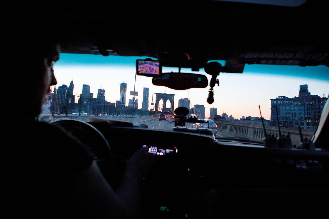 Bounty hunter Vinny Cornwell driving across the Brooklyn Bridge.