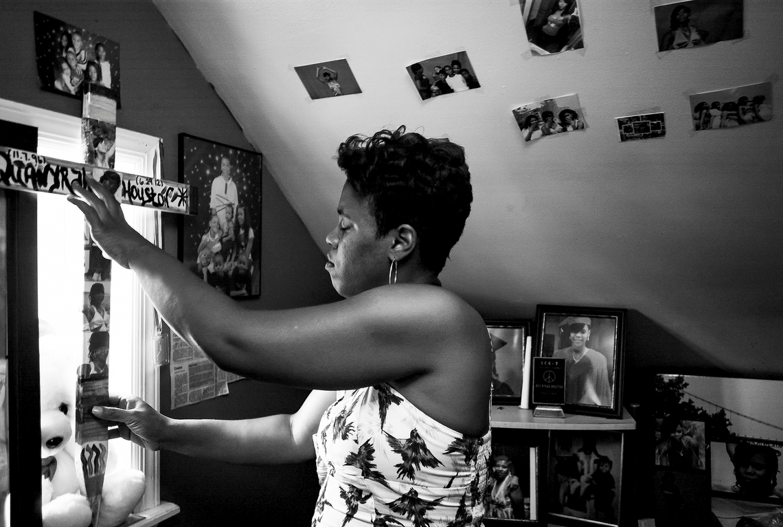 Montika Lowe displays a memorial cross in her daughter's room on June 27, 2013. The daughter, Qua'Nyrah Houston, 15, and her boyfriend were killed in 2012 in a fire, which was later ruled by police to be arson. No one has been charged in the killing.