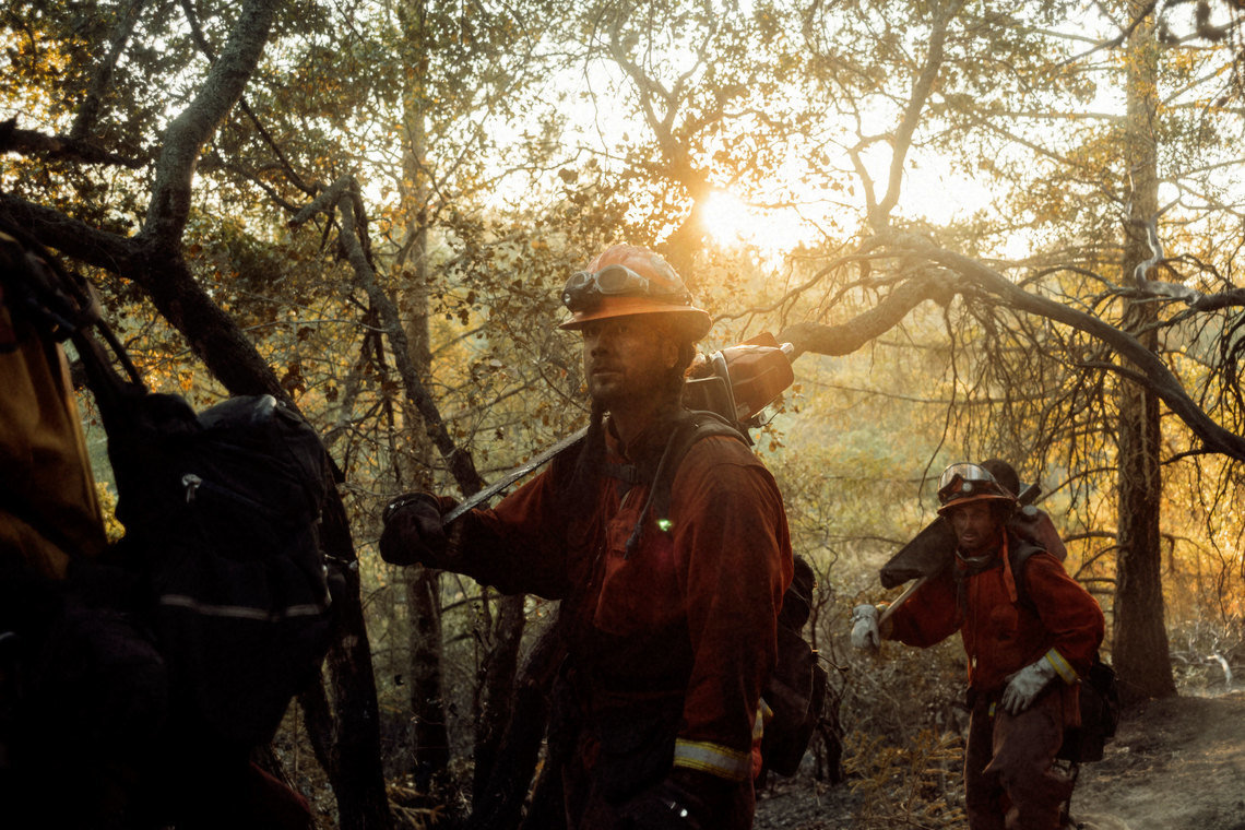 The Antelope fire crew marches into action in Sonoma County, Calif. Much of a crew's work is done by cutting lines into burning brush with power tools so that water lines can be brought in to douse the fire.