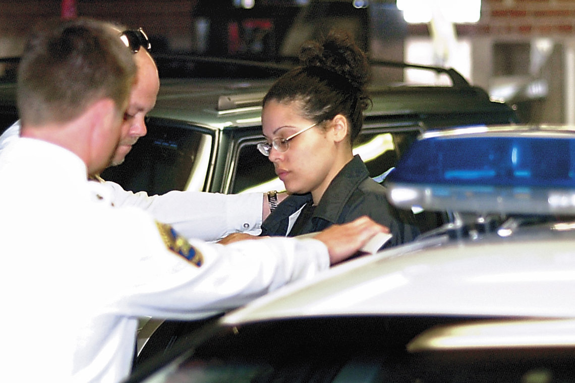 Shonda Walter, right, is placed into a police car in Lock Haven, Pa., after being found guilty of first degree murder in April 2005.
