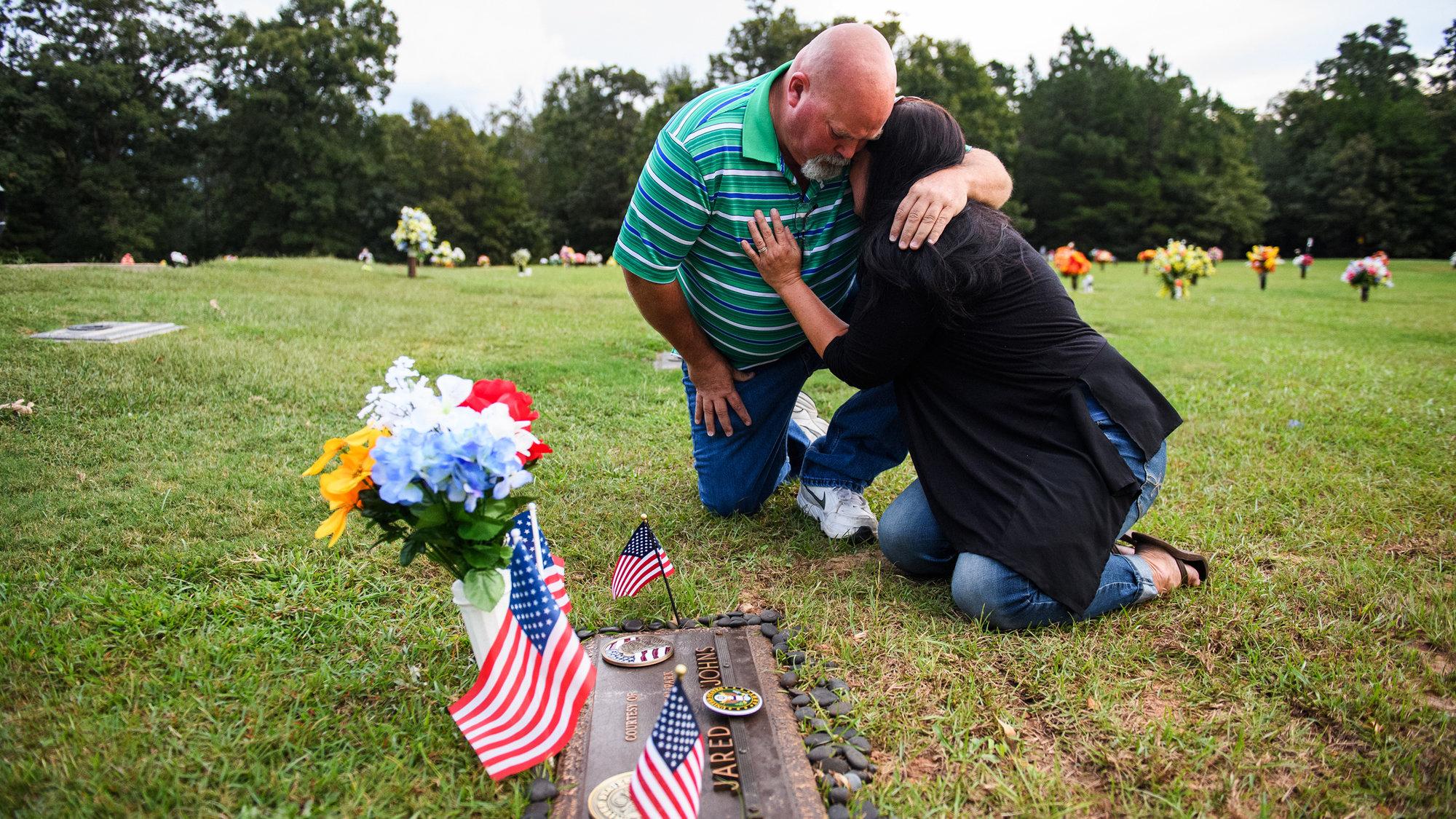 Kevin Johns comforts Kathy Bowling at their son Jared Johns' grave at Cannon Memorial Park in Fountain Inn, South Carolina.