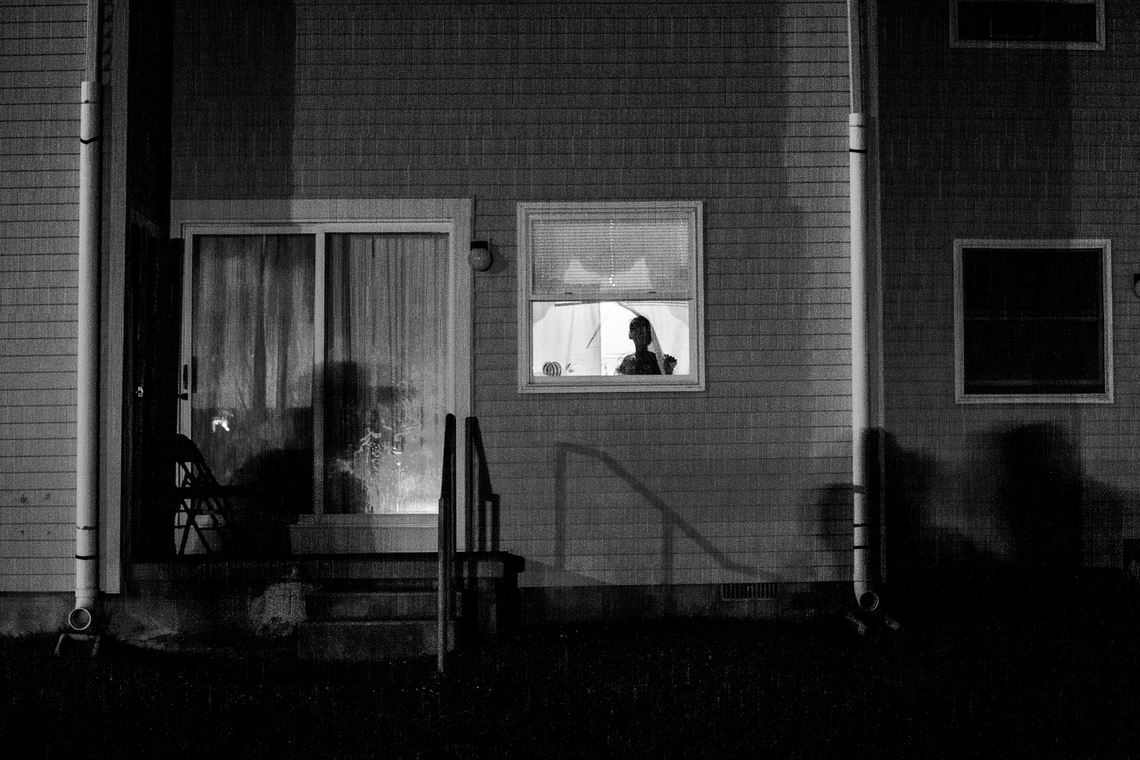A young girl looks out of a window of her home in the Back Maryland neighborhood of Atlantic City on July 14, 2012.