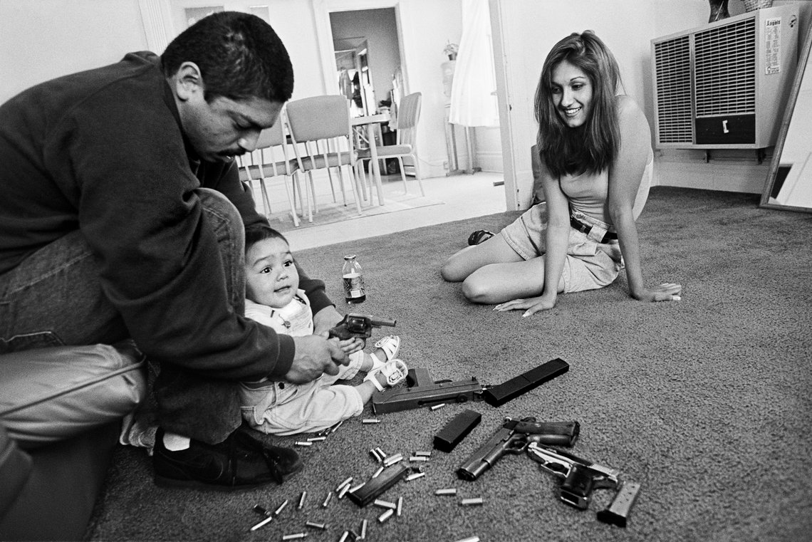 Chivo teaches his daughter how to hold a .32-caliber pistol in the Boyle Heights neighborhood of Los Angeles, Ca., in 1993.