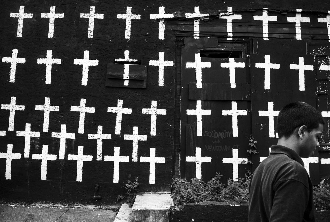 A boy walks by a wall of crosses on Jasper Street in Camden, N.J., on July 17, 2013. There are 67 crosses, each symbolizing a homicide that occurred in 2012.