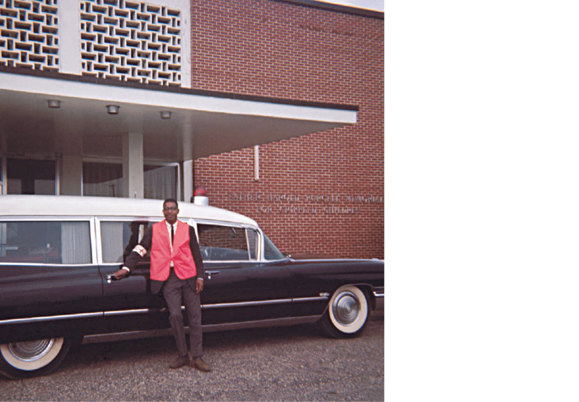 """Dr. Alvin Poussaint, a leader in the health care civil rights movement, with an """"ambulance"""" during the 1965 march from Selma to Montgomery, Ala. Since White hospitals frequently refused to send ambulances for Black patients, Black medical workers repurposed hearses for medical transport. Patients sometimes died in the hearse as the driver searched for a hospital willing to accept a Black person."""