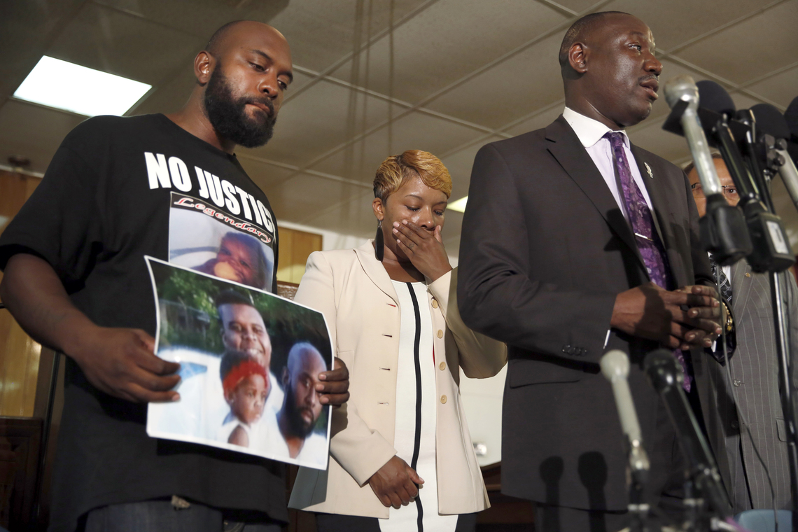Michael Brown's parents, left, at a news conference with their attorney Benjamin Crump on Aug. 11, two days after their son was killed.