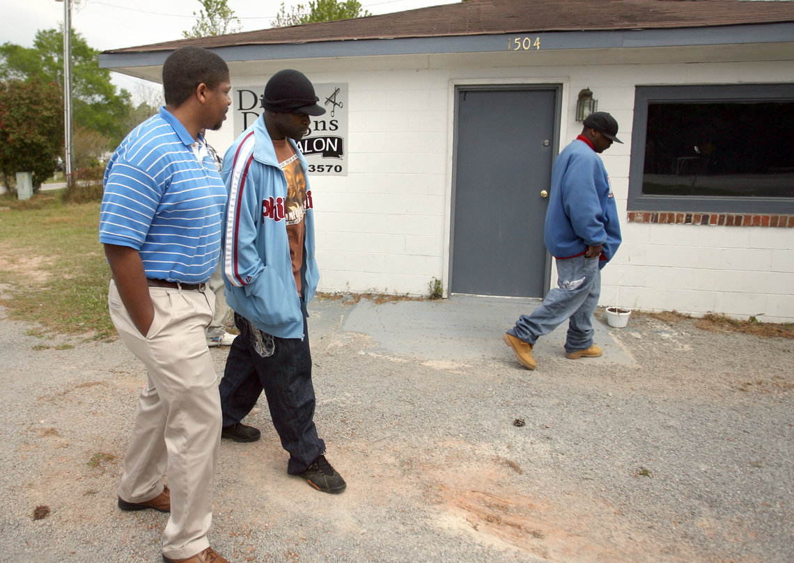 Issac with family at the scene of Bunch's murder. The building now houses a hair salon.
