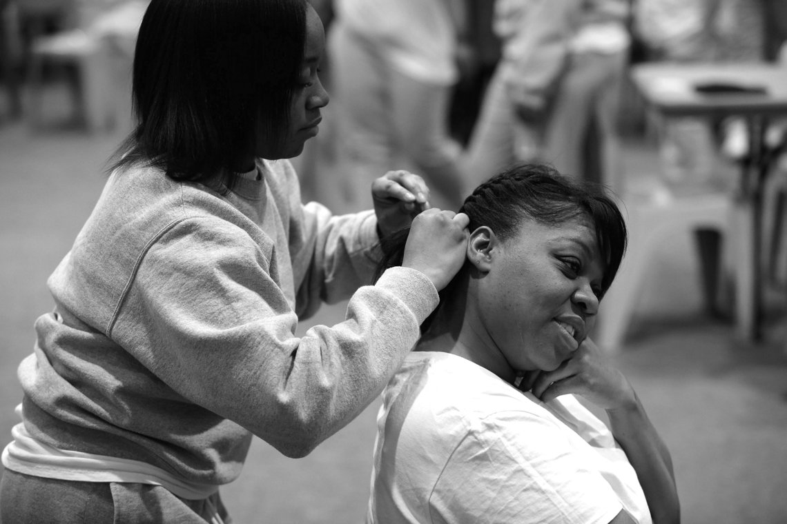 Jamille braided Latashia's hair as they wait for the bus of children to visit Logan Correctional Center.