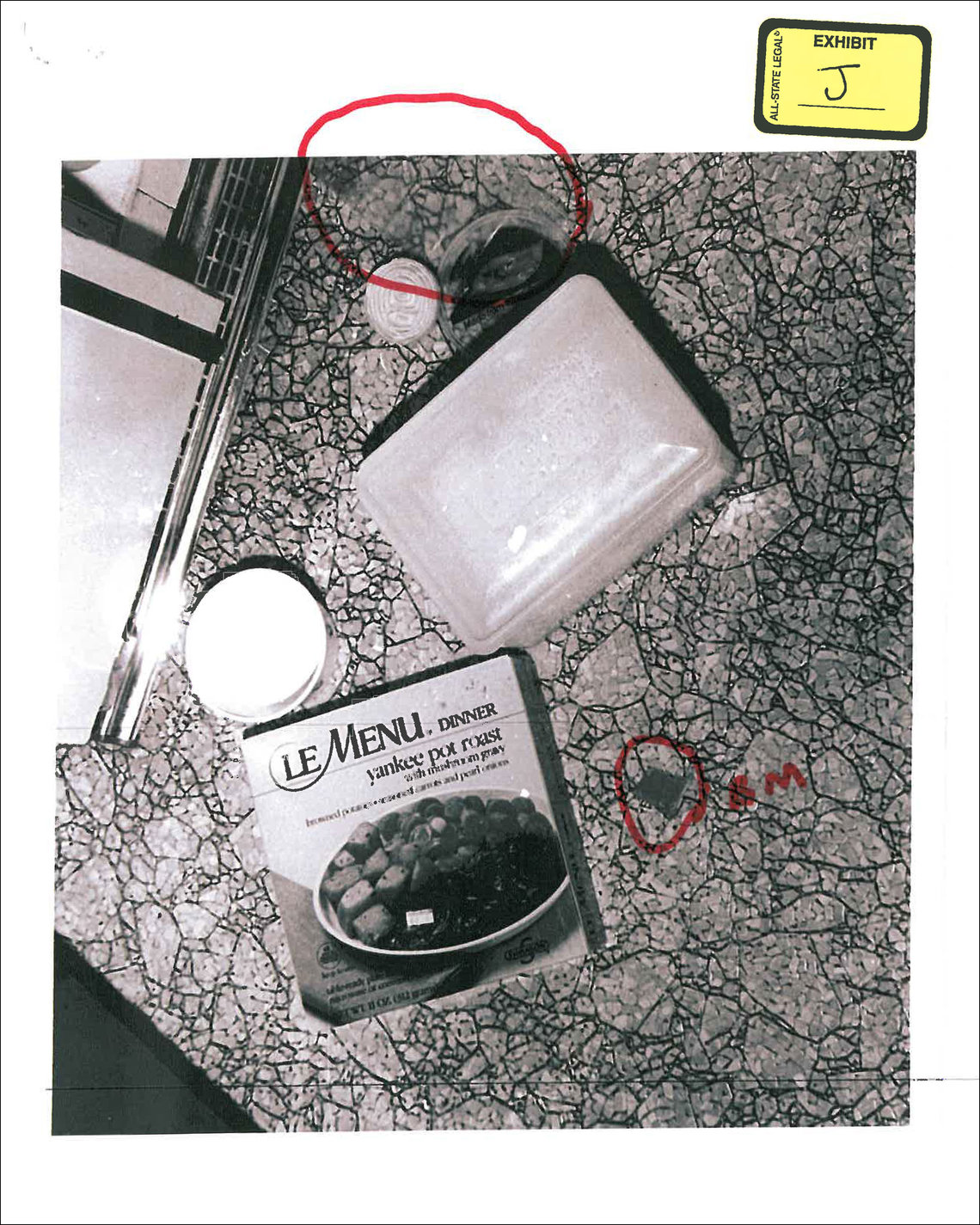 An evidence photo of the food discovered on the floor of Knoernschild's kitchen. At top, circled in red, is the clear cheese wrapper.