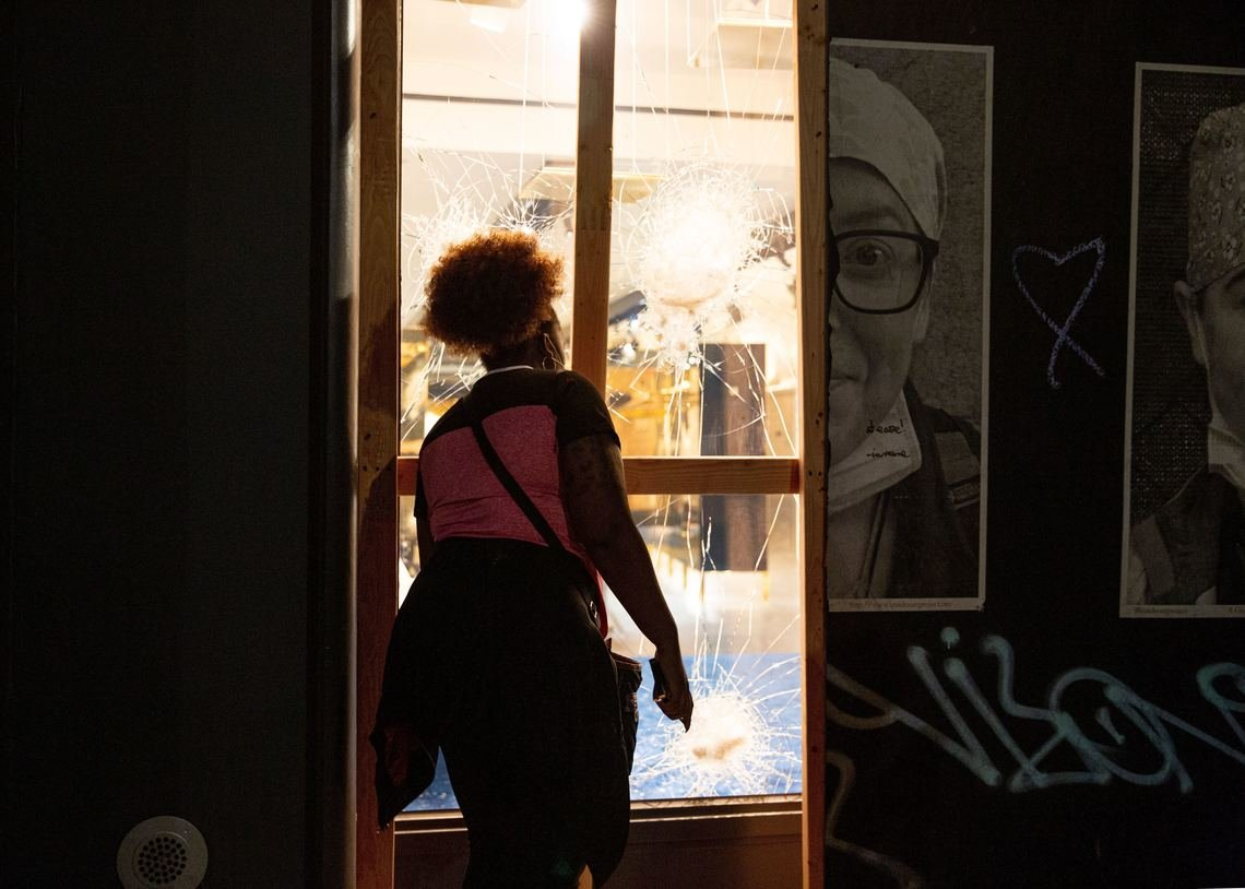 A woman looks through a smashed store window in Soho on Sunday evening. It was one of several retail businesses vandalized or looted. On Monday, major Manhattan stores like Nike and Macy's were also looted.