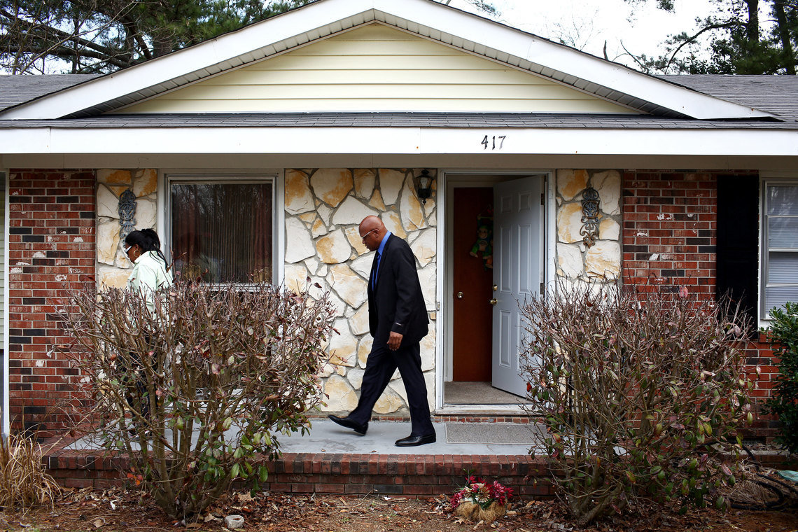 Leon Brown walks behind his sister, Geraldine Brown, outside of a home they shared with several family members in Fayetteville, N.C., after his release from prison.