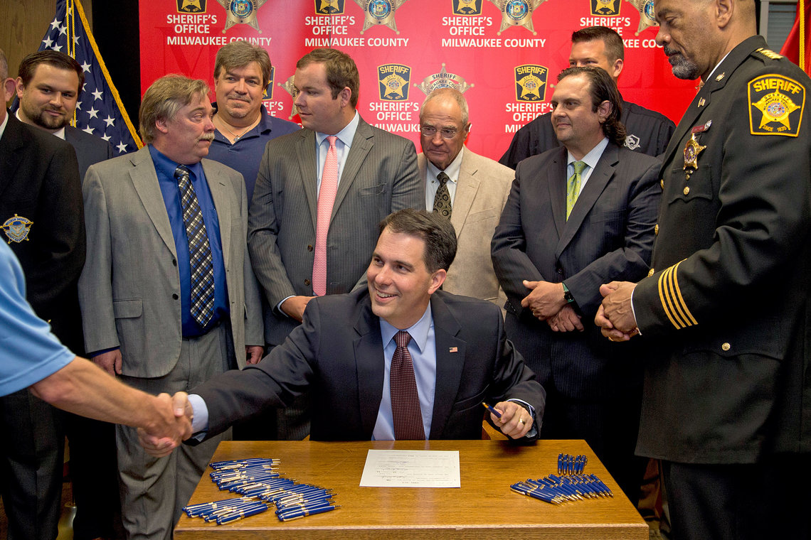 Wisconsin Governor Scott Walker signs a gun bill at the Milwaukee County Sheriff's office on June. 24.