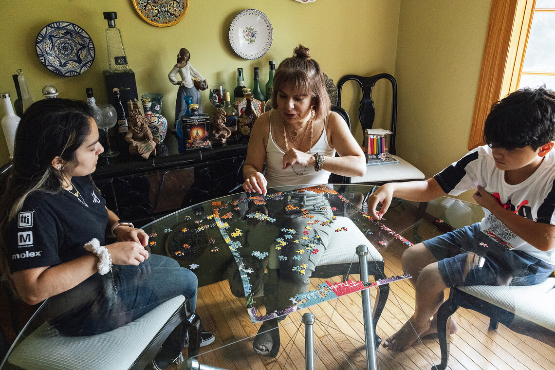 Perez and her children, Isabella and Xavier, work on a puzzle at home in Schaumburg, Ill.