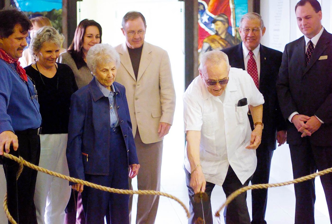 Charles Pearce uses a sword to cut the ribbon (rope) for the Pearce Civil War Collection and Western Art Gallery as his wife Peggy and others look on.