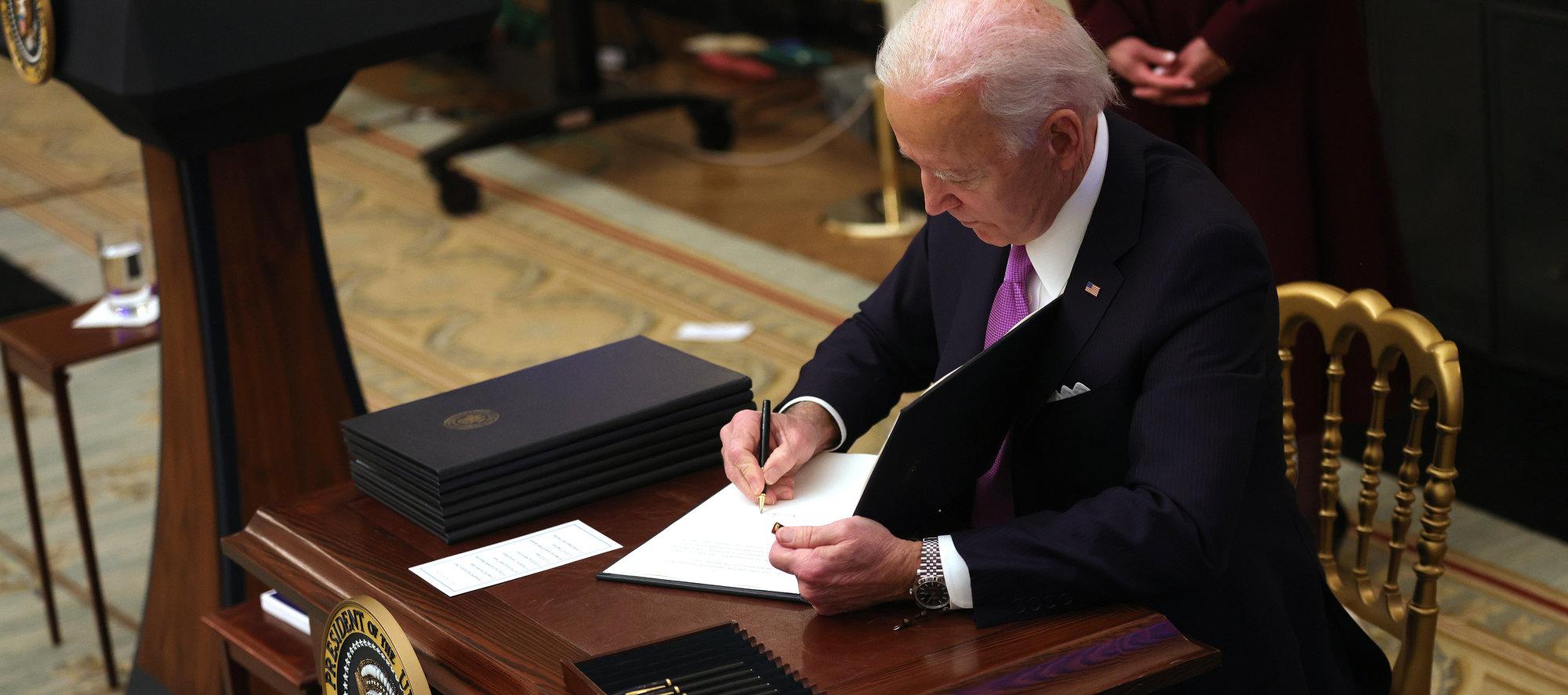 President Joe Biden signs an executive order at the White House in Washington, on Jan. 21.
