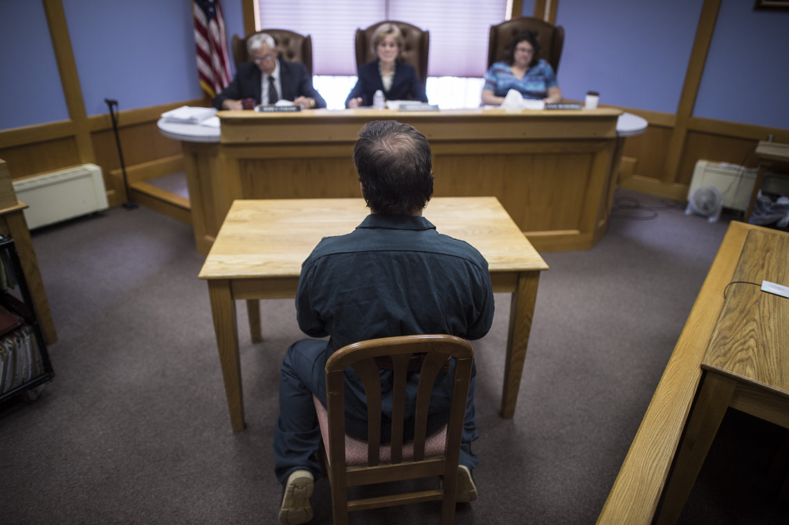 An inmate sits in handcuffs during a parol board hearing at the New Hampshire State Prison for Men in Concord, NH., on July 02, 2015.