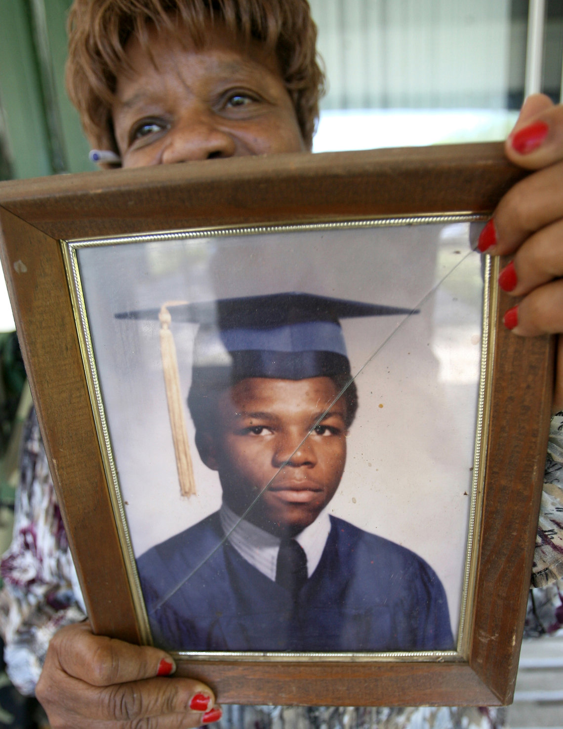 Issac's mother holding a photo of 18-year-old Moochie.