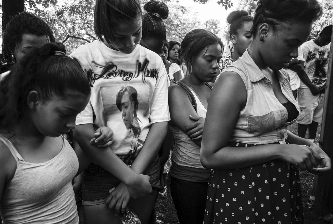Women pray on June 29, 2013, the one-year anniversary of or Qua'Nyrah Houston's death.