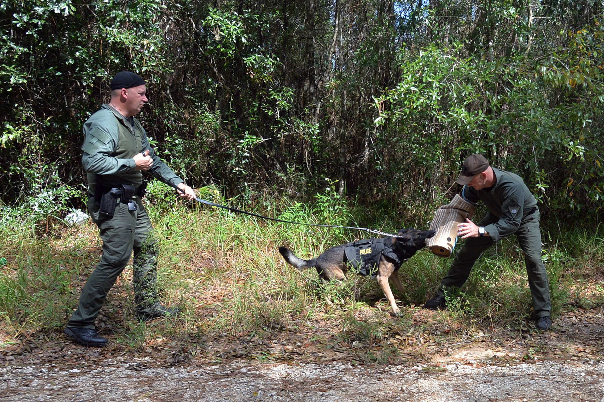 Officer William Byrd, left, commands his police dog during a training exercise in Mobile, Alabama, on Sept. 24, 2020. Officer Justin Washam wears a protective sleeve for a bite demonstration.