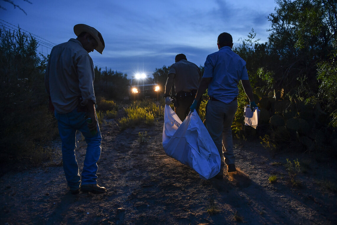 Ranch hand Juan Ramirez, left, looks on as Webb County Sheriff's Deputy Mauro Lopez, front, and Webb County Medical Examiner's Office investigator, Max Cantu, right, carry away the remains of a border crosser from a Laredo, Texas ranch, in 2016.