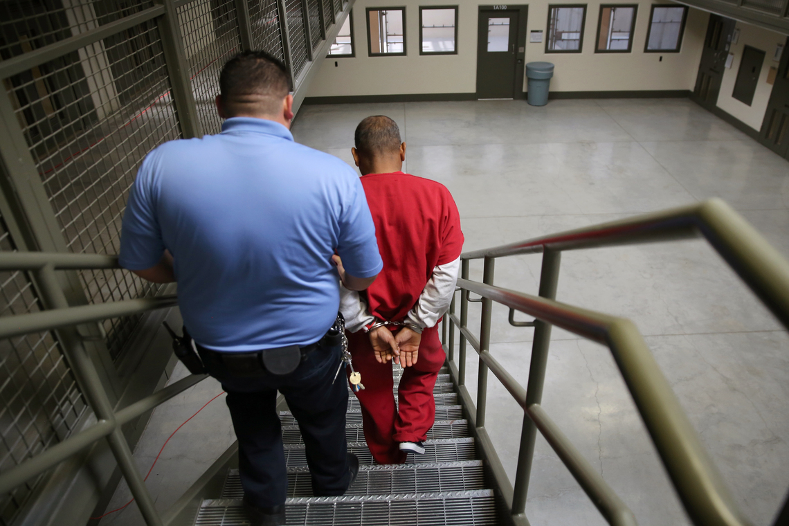 A guard escorting an immigrant detained at the Adelanto Detention Facility in Adelanto, Calif. on Nov. 15, 2013.