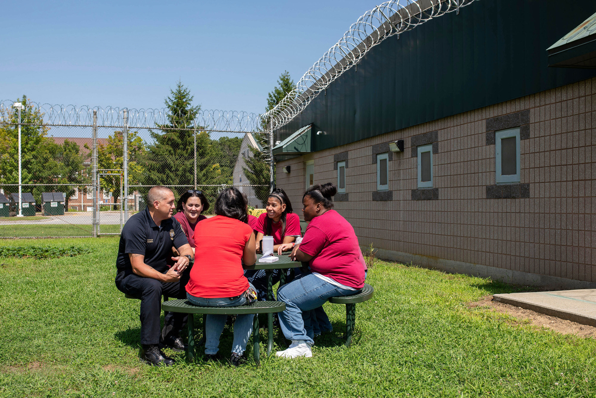 Lt. Russell Hanes, left, and counselor Colleen McClay, in bright red at center, chat with women who are incarcerated at York Correctional Institution in Niantic, Conn., in August.