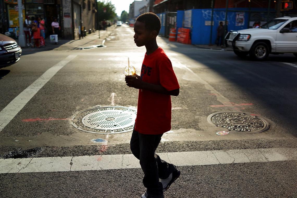 A boy walks down a Crown Heights, Brooklyn street in July 2013.