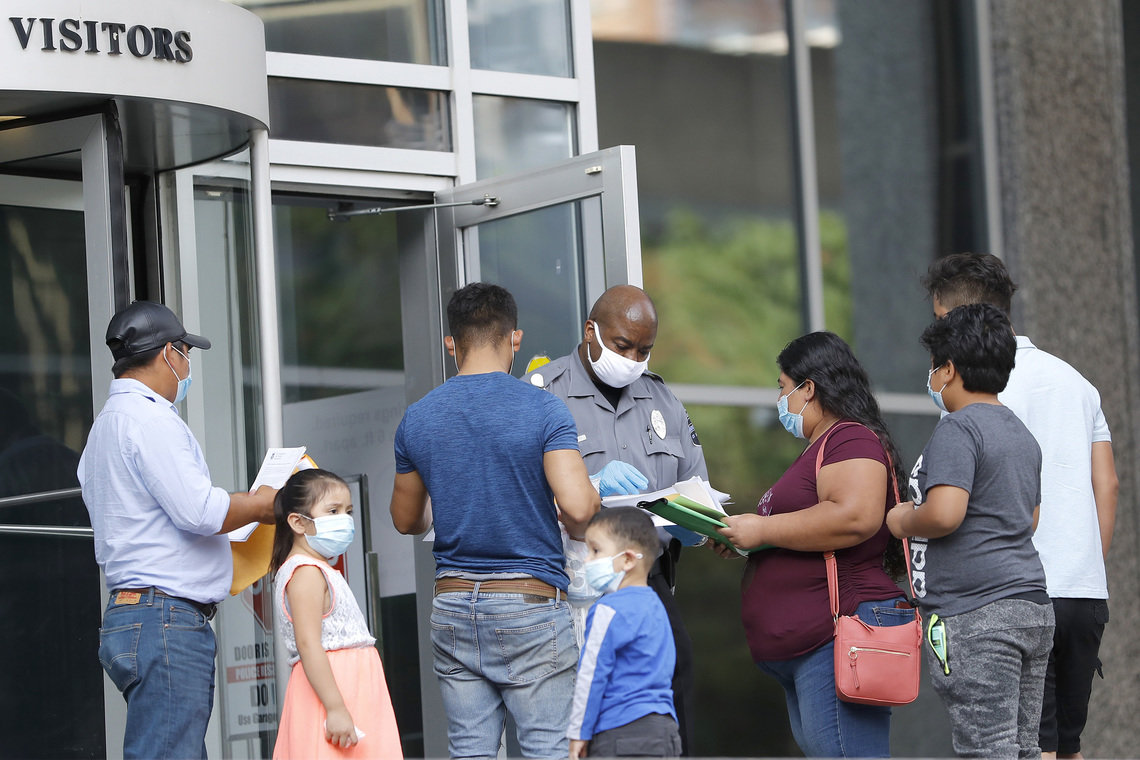 A security officer, center, meets with people outside the immigration court in a federal building in Baltimore to give them a form to come back at a later date because of the coronavirus pandemic, on Monday, July 13, 2020, in Baltimore, Md.