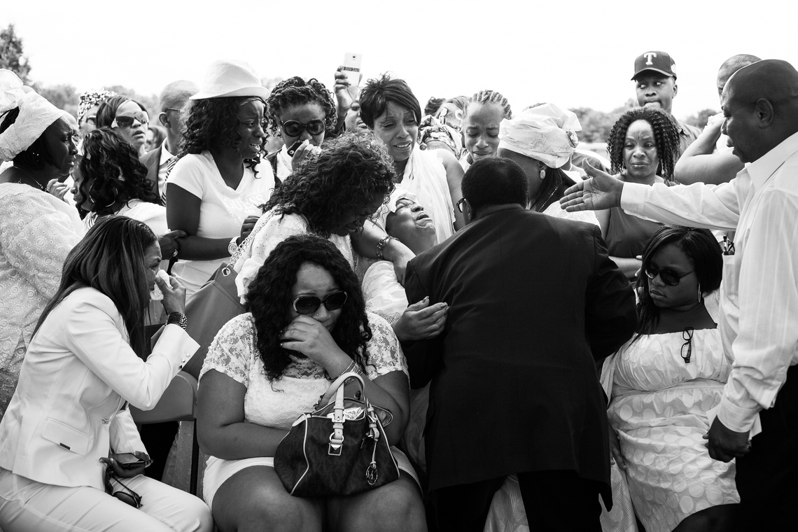 Family members weep as the casket of Alexander Kamara is lowered into the ground on Saturday, July 21, 2012. Kamara, 16, was a promising student and soccer player who wanted to go to college. He was killed in the crossfire of a shooting that took place during an afternoon soccer tournament in Wilmington, Del.