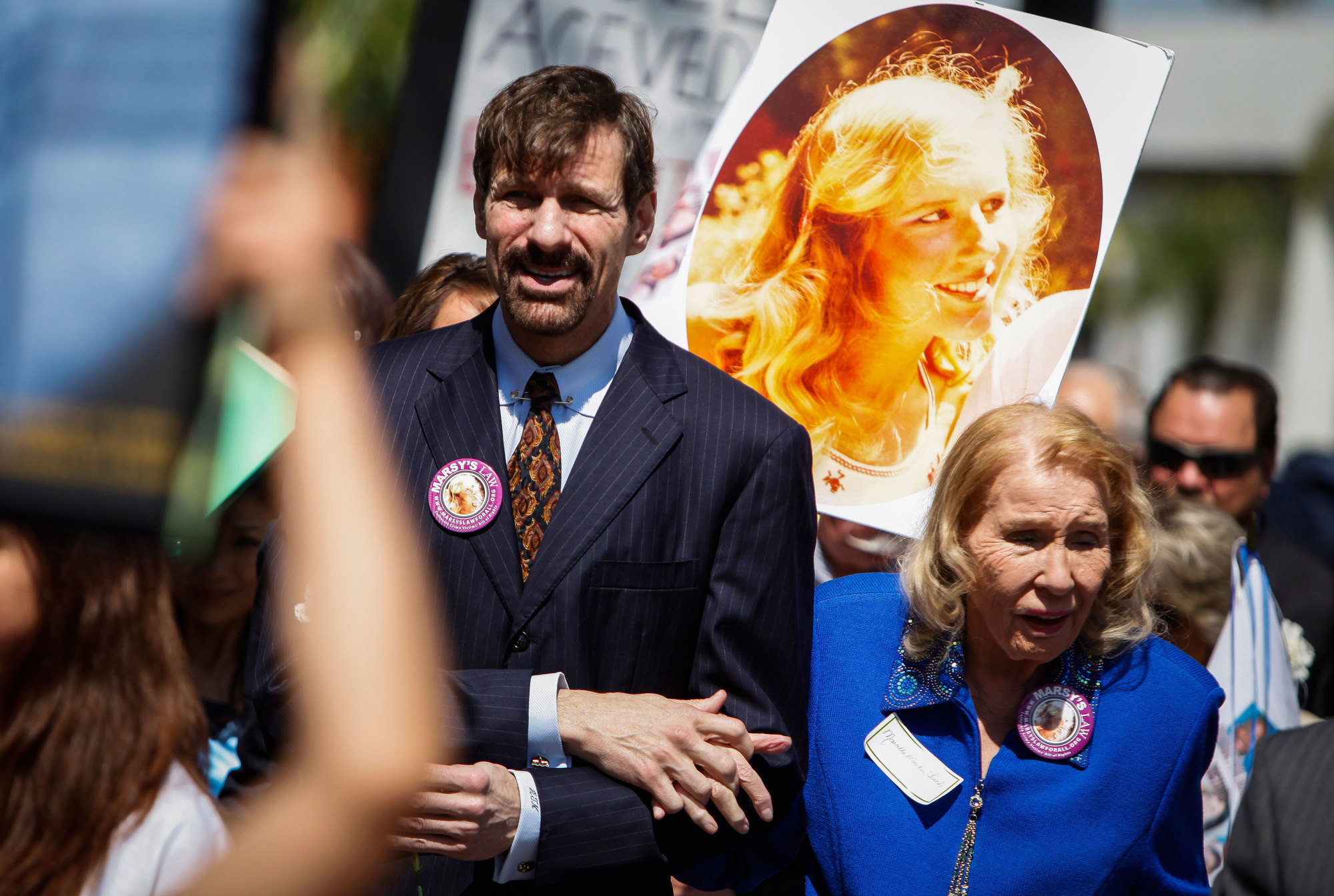 Henry T. Nicholas III, left, and his mother, Marcella Leach, with a photo of his sister, Marsy Nicholas, during the Orange County Victims' Rights March and Rally in 2013.