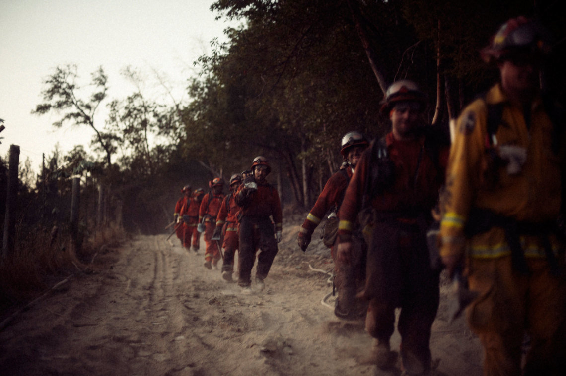 Antelope Conservation Camp firemen are led in formation by a CAL FIRE captain during October's fires in Sonoma County. The inmate firefighter camps have their origins in the prisoner work camps that built many of the roads across remote parts of California in the early 1900's.