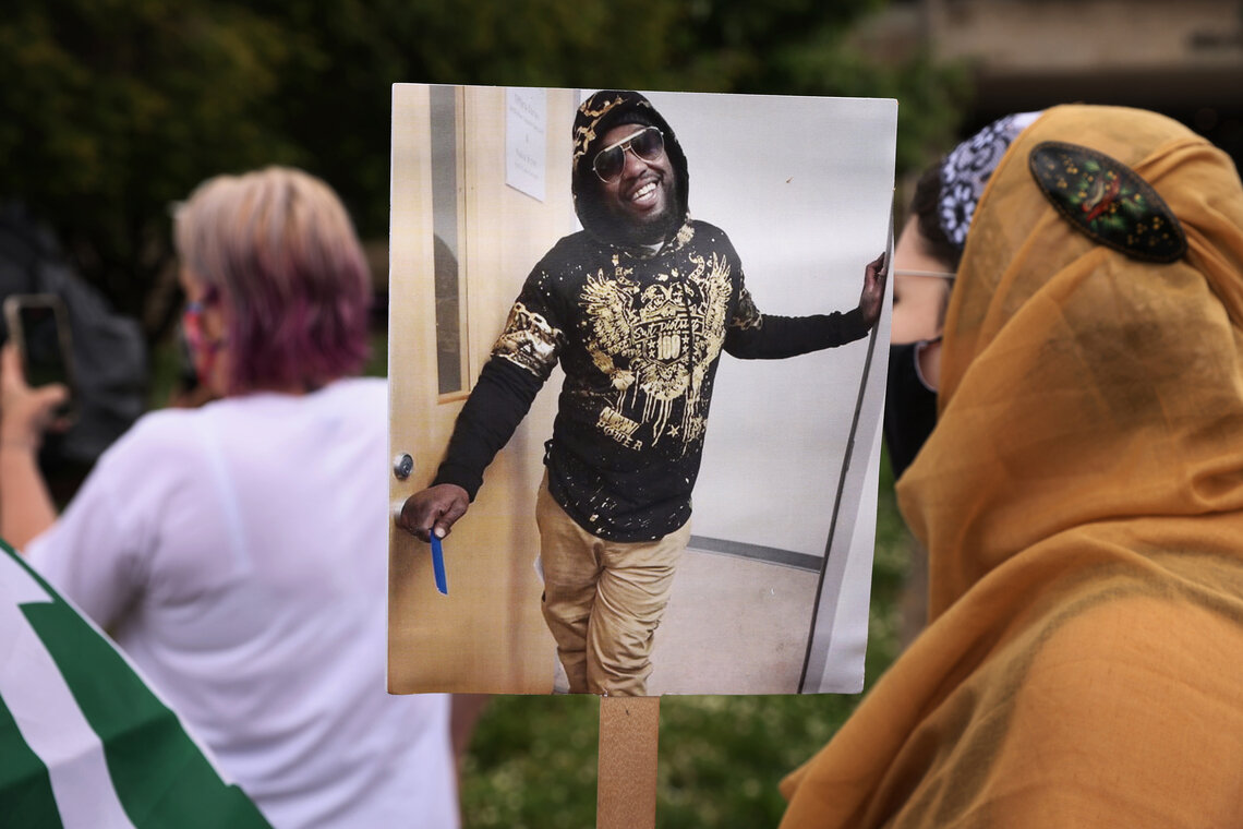 A protester at a May 3, 2021 demonstration holds a picture of Marcus Smith, who died after police hogtied him on a Greensboro, N.C. street in September 2018.