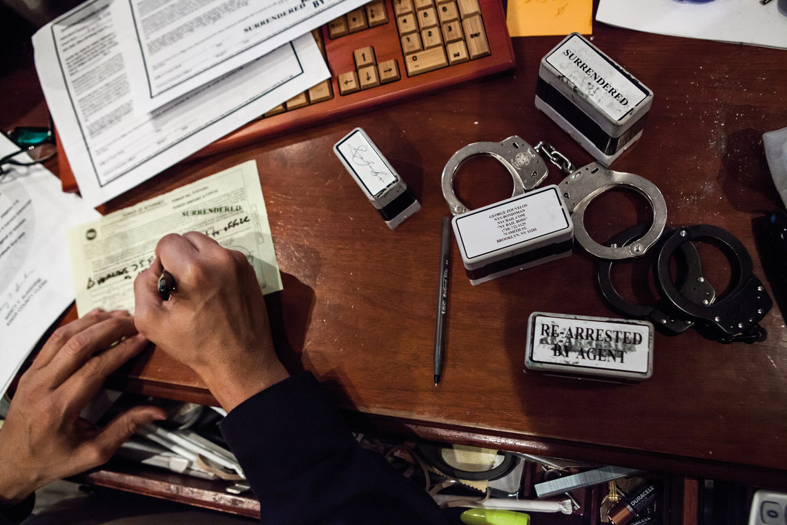 Handcuffs, stamps, and documents cover Zouvelos's desk.