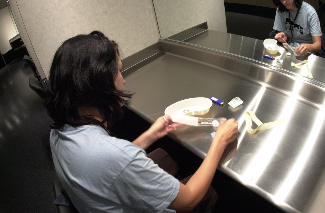 An peer counselor at Insite demonstrates how someone would use one of their injection booths.