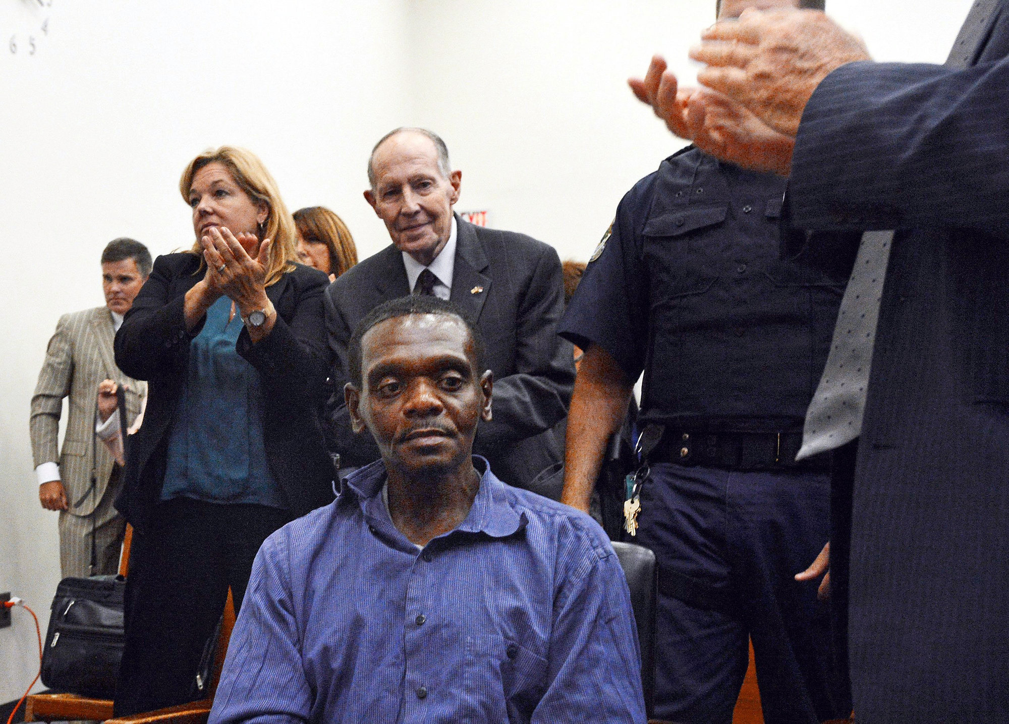 'Bev' Lake, Jr., center, stands behind Henry McCollum after a judge declared McCollum innocent of murder in September 2014. McCollum was exonerated through the innocence inquiry commission that Lake created.