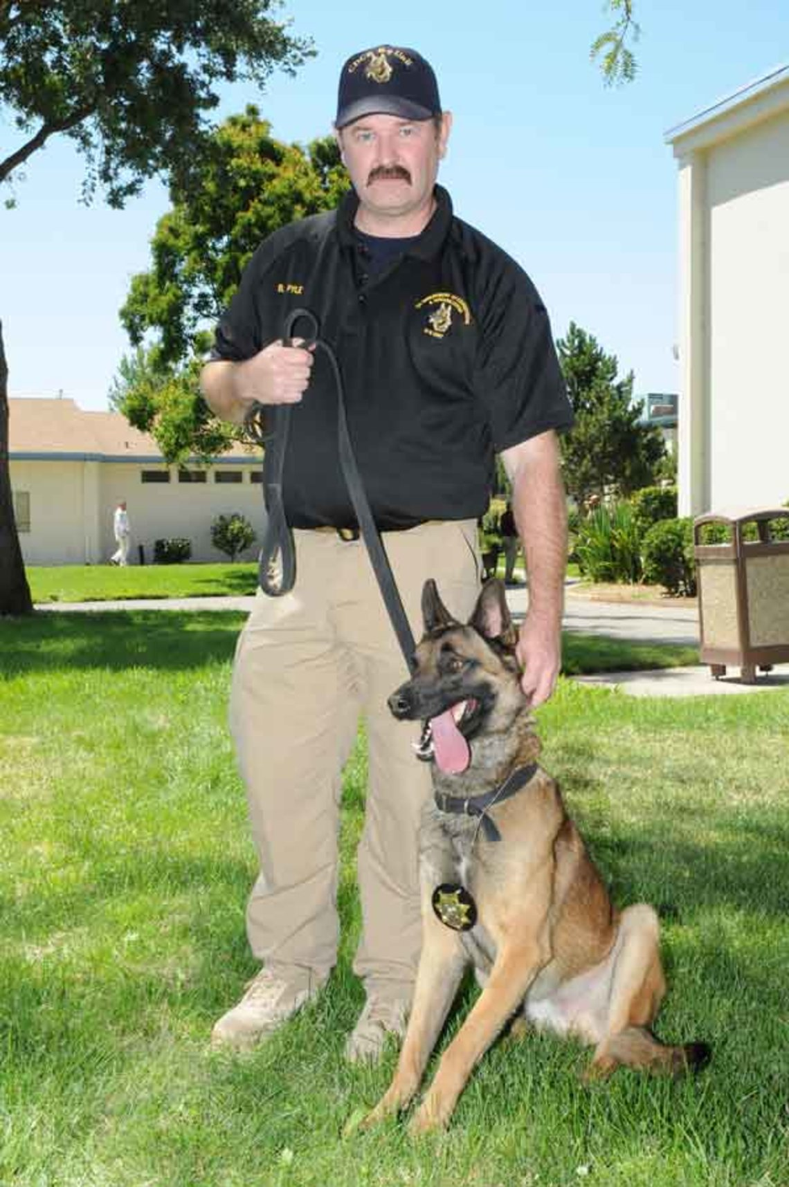 Drako, the dog who found more than a thousand cell phones in California prisons, with his handler Bryan Pyle.