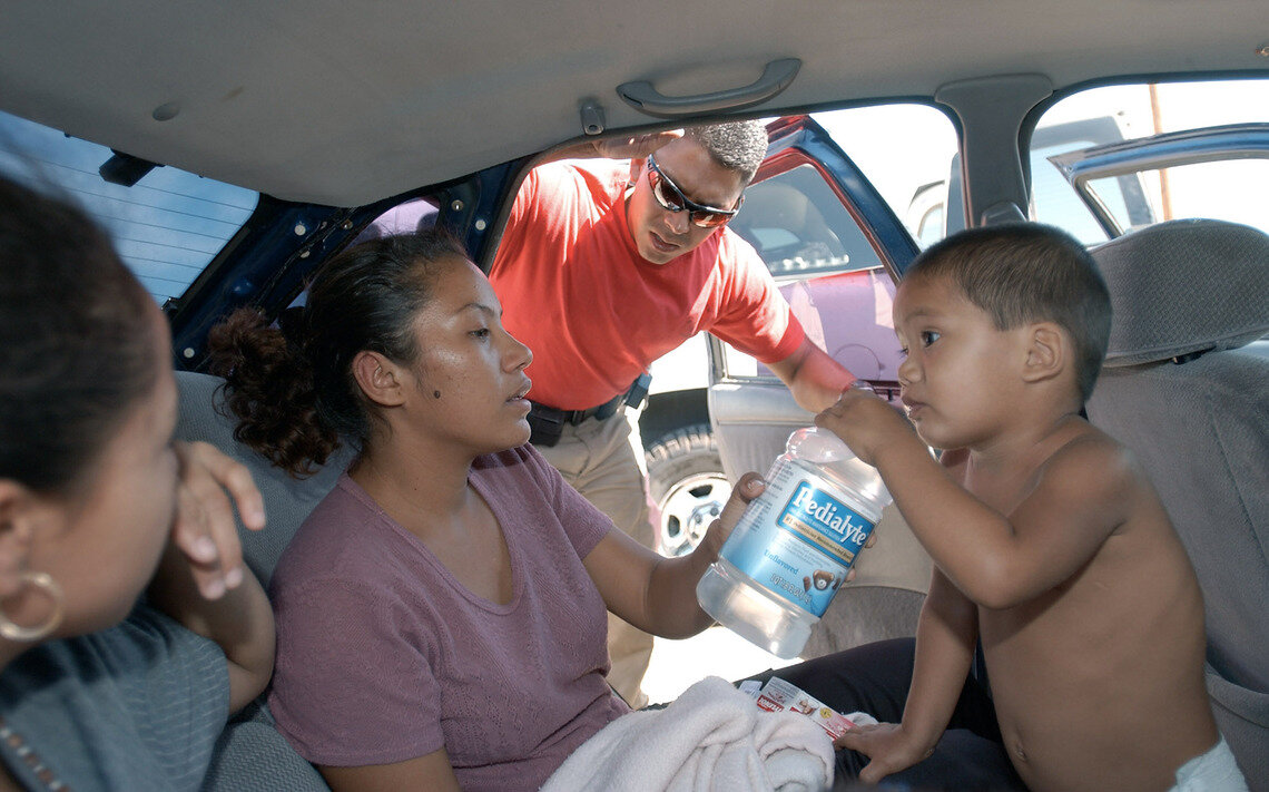 U.S. Border Patrol Search, Trauma, and Rescue (BORSTAR) team member Rick Cardiel watches as a young dehydrated child drinks Pedialyte in the back of a car, near Yuma, in July of 2002.