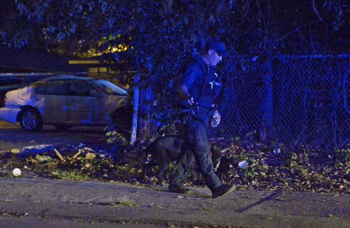 A Baton Rouge police officer and his K-9 at the scene of a shooting in October of 2017, in Baton Rouge, La.