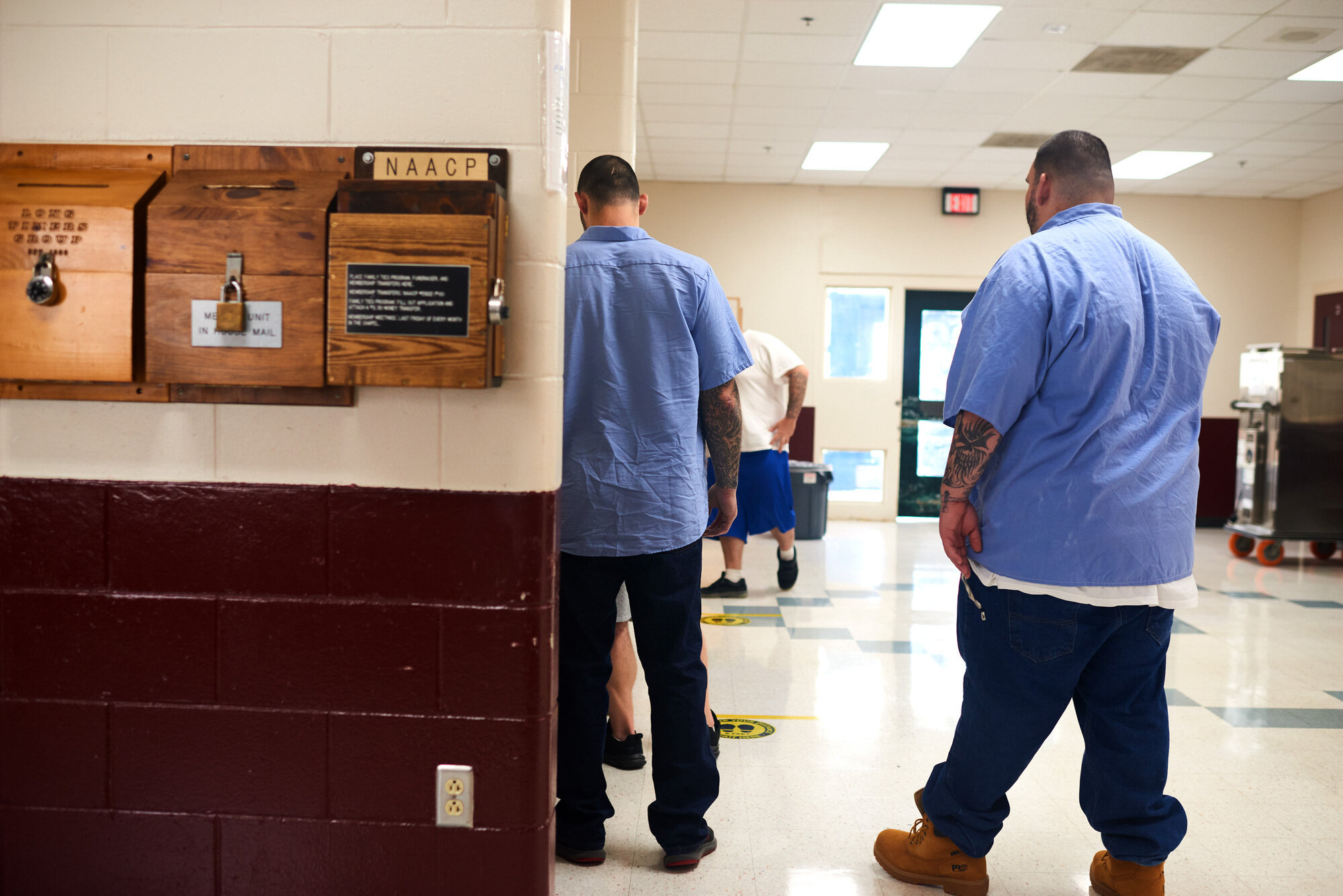 People incarcerated at Maine State Prison wait in the 6:30 a.m. med line on July 28, during which some receive methadone or buprenorphine to combat opioid addiction.