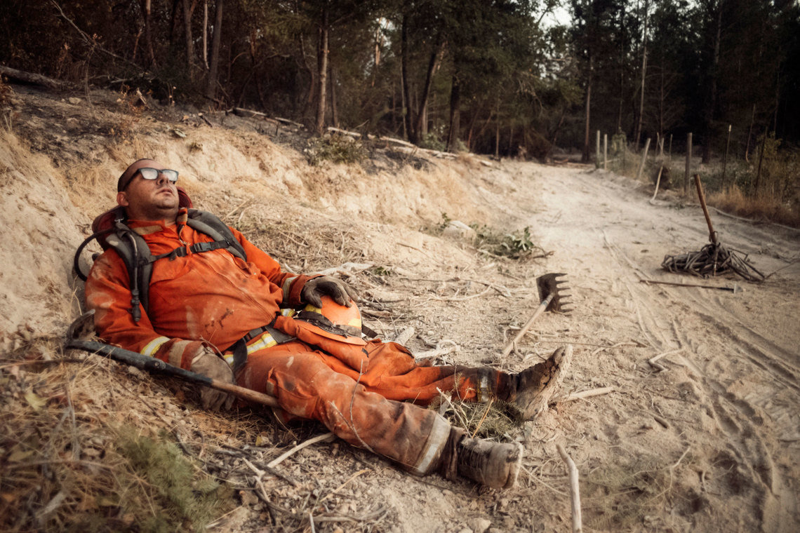 Eduardo Amezcua, exhausted from fighting wildfire in Sonoma County, takes a break on the side of a fire trail.