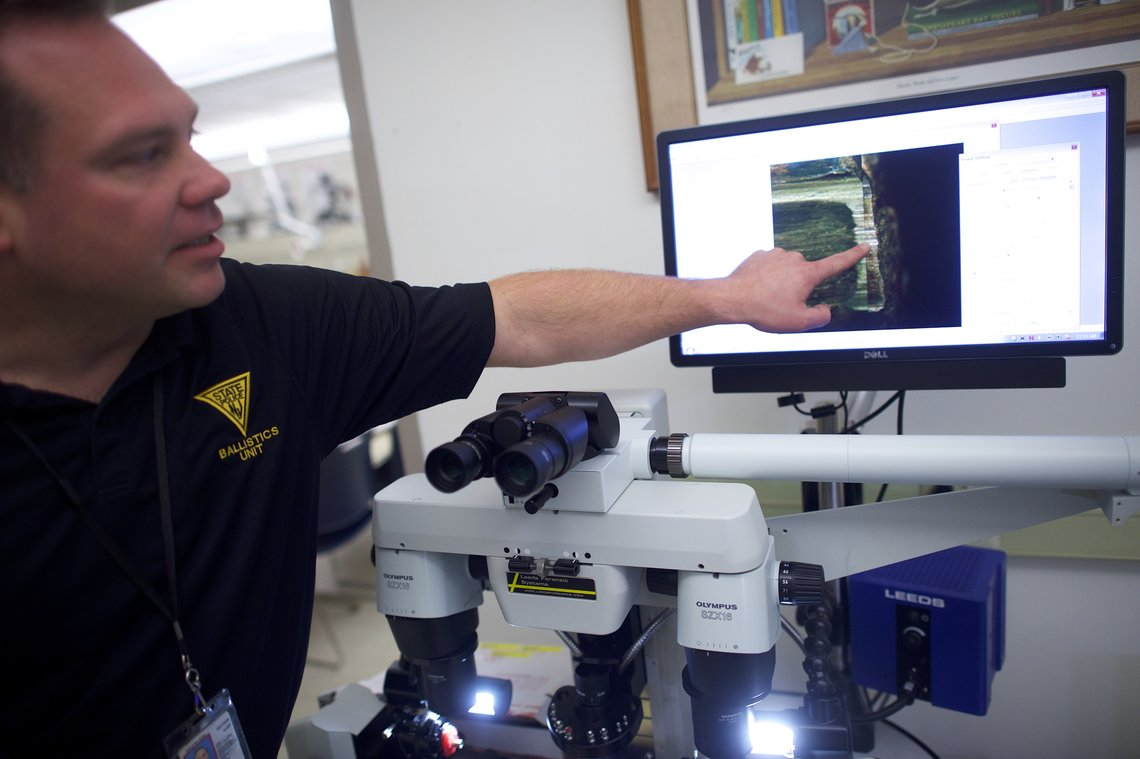 Using a microscope, New Jersey State Police Detective Edward Burek compares bullets test-fired from a gun used in a crime. The corresponding shell casings were entered into NIBIN.