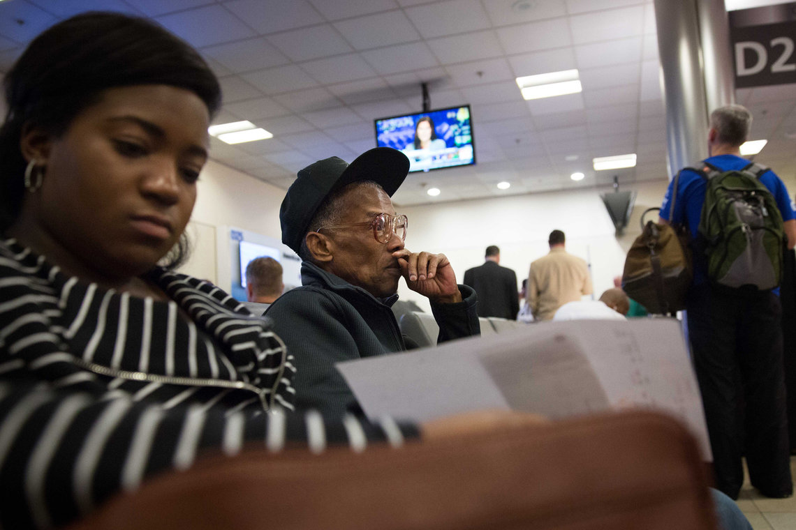 Elston sits at his gate at the Atlanta International Airport waiting for his flight to Philadelphia with his social worker.